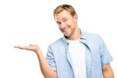 Jeune homme heureux montrant le copyspace vide sur le fond blanc Photographie stock