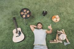 Jeune homme heureux montrant le pouce et se reposant sur l'herbe avec la guitare et la nourriture pour le pique-nique Photos libres de droits