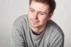 Jeune homme heureux occasionnel à la mode avec la barbe légère, sur le CCB gris image stock