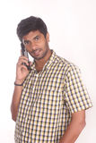 Jeune homme heureux parlant sur le mobile d'isolement Photos stock