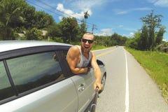 Jeune homme heureux prenant la photo de Selfie avec Smartphone sur le bâton de Monopod Hippie faisant la photo de voyage par la r Photographie stock