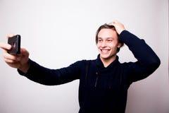Jeune homme heureux prenant la photographie d'autoportrait par le téléphone intelligent Photo stock