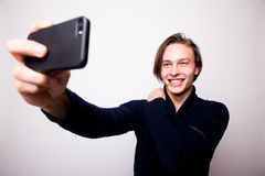Jeune homme heureux prenant la photographie d'autoportrait par le téléphone intelligent Photographie stock