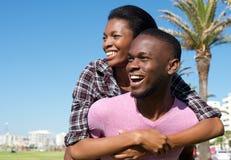 Jeune homme heureux ramenant l'amie attirante sur le sien Images stock