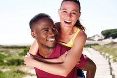 Jeune homme heureux ramenant l'amie attirante sur le sien Photo stock