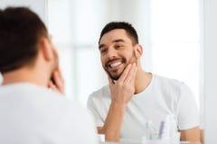 Jeune homme heureux regardant pour refléter à la maison la salle de bains Image stock