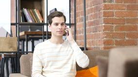 Jeune homme heureux s'asseyant au sofa dans l'espace de travail créatif, répondant à un appel téléphonique Image libre de droits