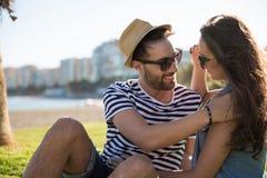 Jeune homme heureux s'asseyant dehors avec l'amie la touchant Photo stock