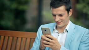 Jeune homme heureux s'asseyant en parc et à l'aide du smartphone banque de vidéos