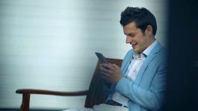 Jeune homme heureux s'asseyant en parc et à l'aide du smartphone clips vidéos