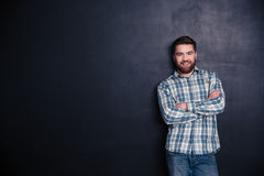 Jeune homme heureux se tenant avec des bras pliés Photographie stock