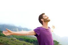 Jeune homme heureux se tenant en nature avec la diffusion de bras ouverte Image stock