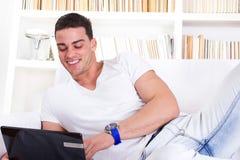 Jeune homme heureux se trouvant sur le sofa travaillant sur l'ordinateur portable photographie stock