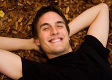 Jeune homme heureux souriant dans des lames d'automne Photographie stock