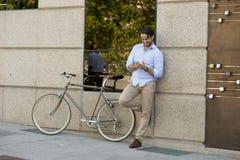 Jeune homme heureux souriant utilisant le téléphone portable sur vélo frais de vintage le rétro Images stock