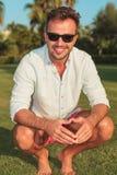 Jeune homme heureux tapi souriant pour l'appareil-photo Photos libres de droits