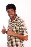 Jeune homme heureux te donnant des pouces sur le fond blanc Photographie stock libre de droits