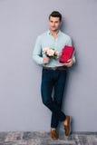 Jeune homme heureux tenant le boîte-cadeau et les fleurs Photographie stock