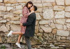 Jeune homme heureux tenant sa femme dans des ses bras sur le fond en pierre photographie stock