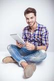 Jeune homme heureux tenant un ordinateur de protection de comprimé Photographie stock