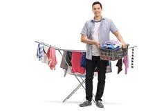 Jeune homme heureux tenant un panier de blanchisserie devant un habillement photos stock
