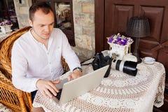 Jeune homme heureux travaillant sur l'ordinateur portable dehors Photographie stock