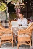 Jeune homme heureux travaillant sur l'ordinateur portable dehors Photo stock