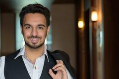 Jeune homme indien heureux souriant tout en tenant la veste dans le corri photos libres de droits