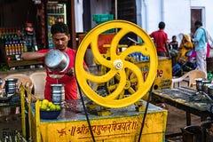 Jeune homme indien rendant le jus de citron au chameau de Pushkar juste Photographie stock