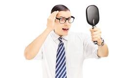 Jeune homme inquiété vérifiant les cheveux de éclaircissement dans le miroir Image stock