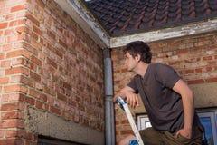 Jeune homme inspectant le mur d'une vieille maison Photographie stock libre de droits