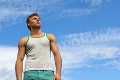 Jeune homme intense sur le fond de ciel bleu Image stock