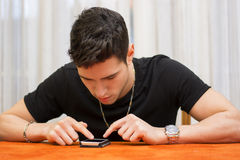 Jeune homme introduisant un message textuel à son téléphone photo libre de droits