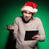 Jeune homme irrésolu de Santa tenant une protection de comprimé Photos stock
