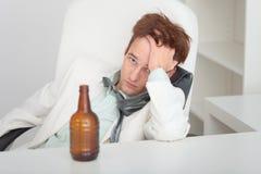 Jeune homme ivre au bureau avec une bouteille à bière Image stock