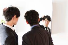 Jeune homme japonais d'affaires fixant au miroir avec l'ami Photos libres de droits