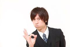 Jeune homme japonais d'affaires montrant le signe parfait Images stock
