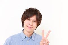 jeune homme japonais montrant un signe de victoire Images libres de droits