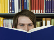 Jeune homme jetant un coup d'oeil au-dessus du livre ouvert Image stock