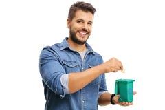 Jeune homme jetant un morceau de déchets dans un bac de recyclage Photo libre de droits