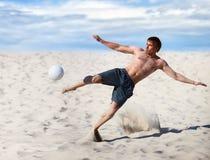 Jeune homme jouant au football Image stock