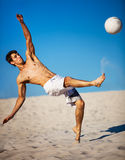 Jeune homme jouant au football Photo stock