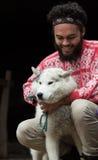 Jeune homme jouant avec le chien devant la maison en bois Images stock
