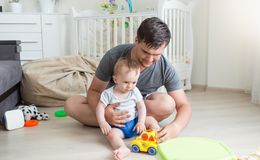 Jeune homme jouant avec ses 10 mois de bébé garçon avec les jouets colorés Photos stock