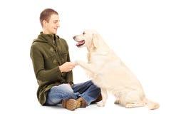 Jeune homme jouant avec un chien de chien d'arrêt Image libre de droits