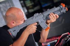 Jeune homme jouant avec un fusil de chasse de jouet Images libres de droits