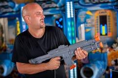Jeune homme jouant avec un fusil de chasse de jouet Photographie stock libre de droits