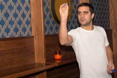 Jeune homme jouant des dards dans un club Images libres de droits