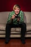 Jeune homme jouant des jeux vidéo Photographie stock libre de droits
