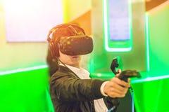 Jeune homme jouant des verres de réalité virtuelle de jeux vidéo gai photos stock